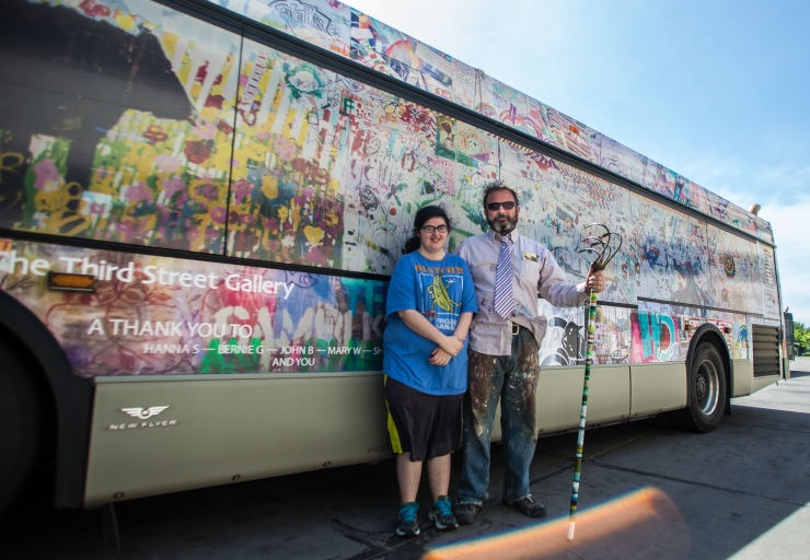Hannah Saagge, left, and Adam Kemp pose for a portrait in front of the bus in downtown Grand Forks, ND on Wednesday, June 8, 2016. (Joshua Komer/Grand Forks Herald)