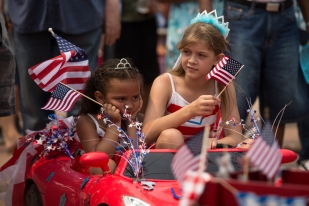 Bella Walker, left, and Alainna walker sit in their big wheel after the parade in downtown Grand Forks, ND on July 4, 2015. (Grand Forks herald/ Joshua Komer)