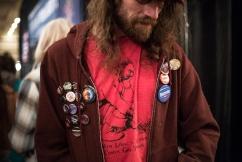 A man poses for a photo sporting many Bernie buttons (Joshua Komer / Grand Forks Herald)