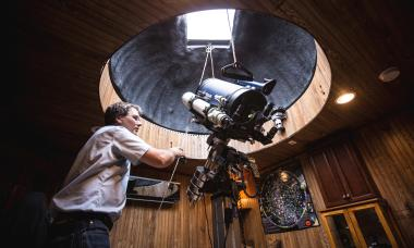 Clint Potulny opens up the dome as he would on a dark night in his home to view the stars with his telescope.
