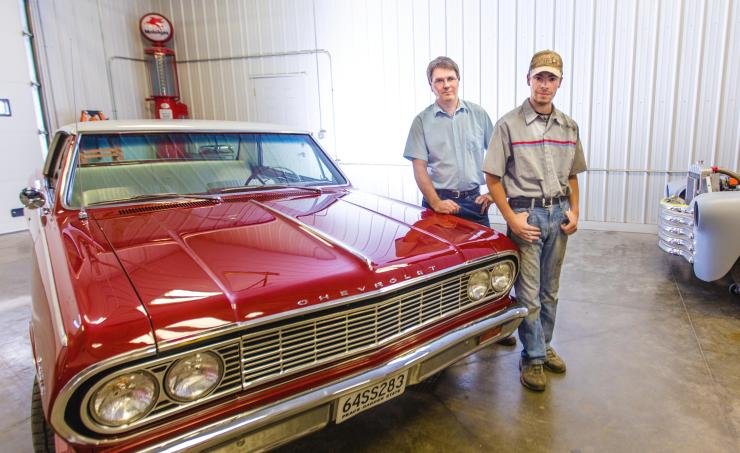 Clint Potulny and his son Austin pose for a portrait next to the family Chevelle SS at his body shop near Fordville, ND on Wednesday, August 31, 2016. (Joshua Komer/Grand Forks Herald)